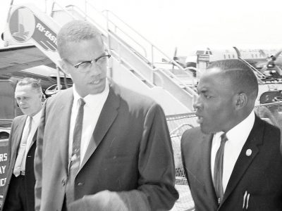 Malcolm X (Left) and local N.O.I. representative Thomas Shabazz (Right) exchange greetings upon his arrival at Columbia Municipal Airport on April 17, 1963. (Image courtesy of The State newspaper)